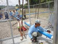 Trainees provide hands-on assistance in installing gas pipes at Biotech in the Philippines.